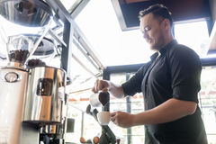 Serious bartender pouring fresh milk into a cup of coffee in a t Stock Photo