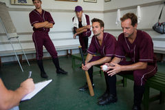Serious baseball team planning while sitting on bench. Serious basbeall team planning while sitting on bench at locker room royalty free stock photography