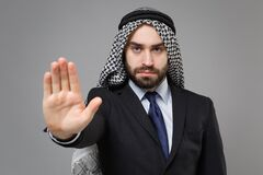 Serious bearded arabian muslim businessman in keffiyeh kafiya ring igal agal classic black suit isolated on gray