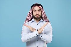 Serious bearded arabian muslim man in keffiyeh kafiya ring igal agal casual clothes  on pastel blue background