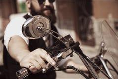 Serious Bearded Biker Man in black jacket sitting on motorbike o Stock Photos