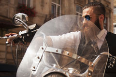 Serious Bearded Biker Man Sitting on a Motorcycle Royalty Free Stock Photography