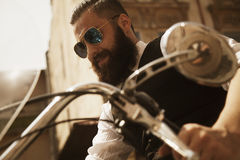 Serious Bearded Biker Man Sitting on a Motorcycle Royalty Free Stock Images
