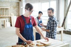 Serious carpentry teacher checking work of students stock image