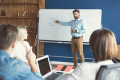 Serious bearded guy teaching his associates in office stock photography