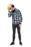 Serious bearded hipster taking off straw hat looking down Royalty Free Stock Images