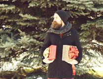 Serious bearded man, handsome hipster, with beard and moustache in black hat, coat and scarf smiles with gift boxes as. Presents on sunny winter day outdoors on stock photography
