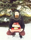 Serious bearded man, handsome hipster, with beard and moustache in black hat, coat and scarf smiles with gift boxes as. Presents on sunny winter day outdoors on stock photos