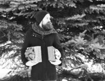 Serious bearded man, handsome hipster, with beard and moustache in black hat, coat and scarf smiles with gift boxes as. Presents on sunny winter day outdoors on royalty free stock photography