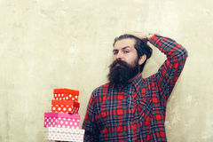 Serious bearded man holding colorful gift boxes stacked in hands. Serious bearded man, caucasian hipster, with long beard and moustache in red plaid shirt Stock Images