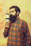 Serious bearded man holding two cosmetic jars royalty free stock photo
