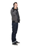 Serious bearded man in jacket and hooded sweatshirt talking on the cellphone looking at camera Stock Photo