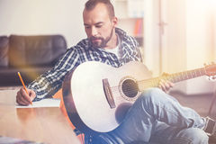 Serious bearded man looking at his writing hand. Not to forget. Delighted composer holding guitar on the leg turning his head to the table, sitting on wheelchair Royalty Free Stock Image
