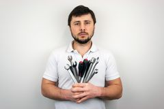 A serious bearded man man in a white T-shirt with a bouquet of wrenches and screwdrivers.  stock photography
