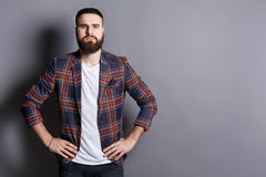 Serious bearded man posing with hands on hips. Serious trendy bearded man posing with hands on hips. Young hipster standing in irritated pose, gray studio Royalty Free Stock Photos