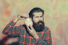 Serious bearded man putting banknote in pink ceramic piggy bank Stock Photo