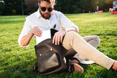 Serious bearded man sitting on grass outdoors getting tablet computer. From his backpack Stock Photos