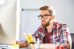 Serious bearded man sitting on workplace and working with computer Stock Photography
