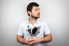 A serious bearded man in a white t-shirt with a bouquet of wrenches and screwdrivers looking to the side.  royalty free stock photography