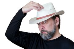 A serious bearded middle-aged man puts on a cowboy hat stock images