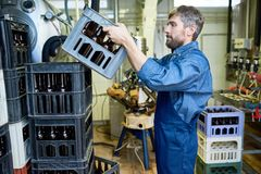 Serious bearded mover in uniform stacking boxes with beer bottle royalty free stock photos