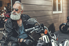 Serious bearded old man on motorbike royalty free stock image