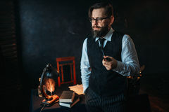 Serious bearded writer in glasses smoking a pipe. Feather, crystal decanter, books and vintage lamp on the desk Royalty Free Stock Image