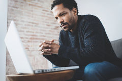 Serious bearded young African man thinking while sitting on sofa at his modern coworking place.Concept of business Stock Photo