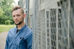 Serious bearded young man in denim shirt stands near background of chain-link and looks straight into the camera.  royalty free stock photo