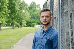 Serious bearded young man in denim shirt stands near background of chain-link and looks straight into the camera.  royalty free stock photos