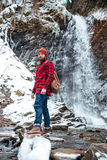 Serious bearded young man standing near mountain waterfall in winter. Serious bearded young man in checkered shirt and hat standing near mountain waterfall in Royalty Free Stock Photos