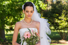 Serious beautiful bride with bouquet in park Royalty Free Stock Photo