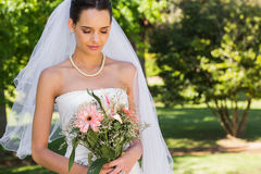 Serious beautiful bride with bouquet in park Stock Photography