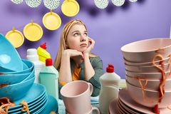 Serious beautiful fair-haired housemaid looks thoughtfully up royalty free stock image