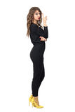 Serious beautiful fashion model in black jumpsuit pointing finger up Stock Photo