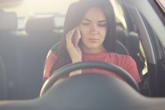 Serious beautiful female talks via cell phone with husband, doesn`t know what to do as stops on road, has no petrol in automobile,. Asks for help, has dark hair Royalty Free Stock Image