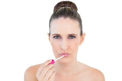 Serious beautiful woman applying lip gloss Royalty Free Stock Photos