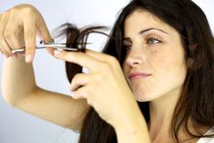 Serious beautiful woman cutting split ends hair Stock Photos