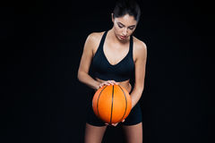 Serious beautiful young fitness girl with orange basketball ball Royalty Free Stock Photo