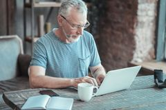 Serious bespectacled man sitting and working with the laptop. Full concentration. Serious bespectacled aged man sitting in the room by the table having Royalty Free Stock Photo