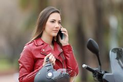 Serious biker calling on phone on a motorbike. Portrait of a serious biker waiting during a phone call to insurance on a motorbike on the street Stock Photography