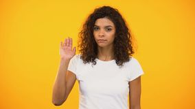 Serious biracial woman showing no gesture to camera against yellow background. Stock footage stock video