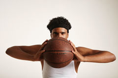 Serious black basketball player with a ball next to his face. Close up shot of a serious young basketball player with an afro wearing headband and white shirt Stock Image