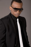 Serious black business man with sunglasses. On grey background stock image