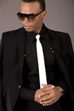 Serious black business man with sunglasses. On grey background royalty free stock photo