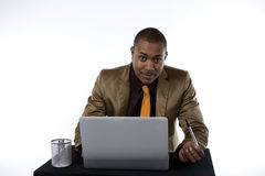 Serious Black Businessman. Black businessman with a serious expression sits at a laptop stock image