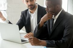 Serious black businessman thinking over business offer looking a. T laptop while caucasian partner explains deal details, successful african investor in suit Stock Photography
