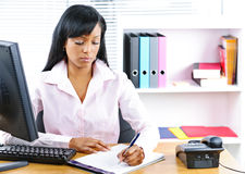 Serious black businesswoman at desk Stock Photo
