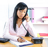 Serious black businesswoman on phone at desk Stock Photo