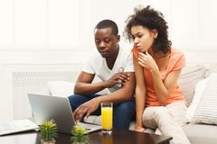 Young african-american couple working on laptop, copy space stock photo